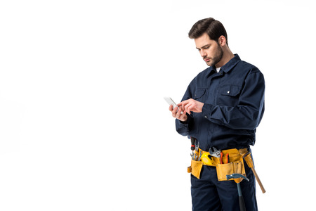 Professional plumber with tool belt using smartphone isolated on white Stock fotó