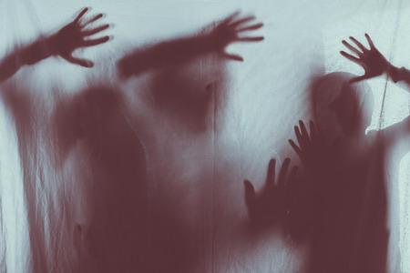 silhouettes effrayantes floues de personnes touchant du verre dépoli avec les mains