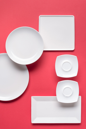 Composition of various white plates on red background