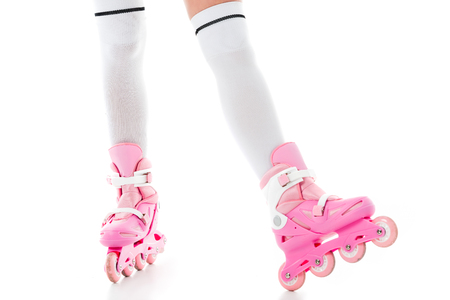 Close-up view of woman in pink inline roller skates isolated on white