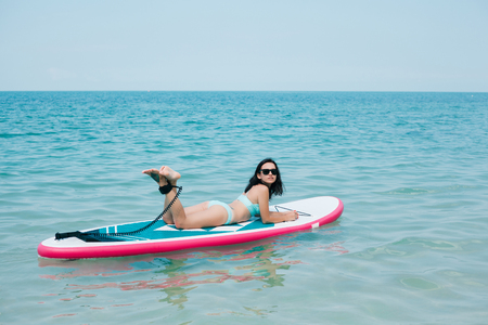 attractive slim girl lying on paddle board on sea at tropical resort