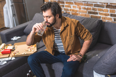 handsome loner drinking water and having hangover at living room