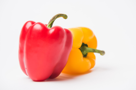 red and yellow fresh bell peppers, on white background