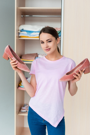 attractive young woman holding high heels in front of cabinet at home Stock Photo