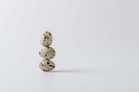 quail eggs stacked on white background