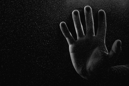 cropped shot of person touching frosted glass with palm in darkness Banque d'images - 111574404