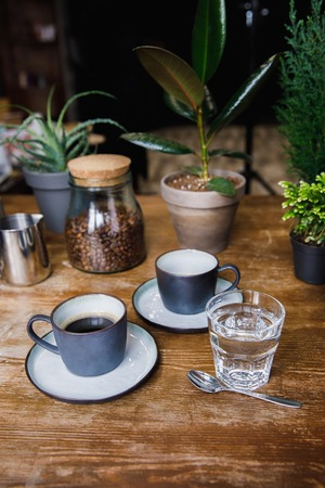 Cups of coffee and glass of water on cafe table Stok Fotoğraf