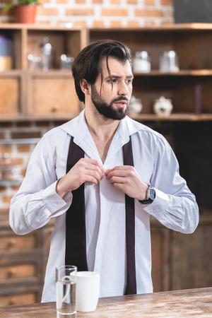 portrait of handsome loner businessman buttoning shirt at kitchen Stock Photo