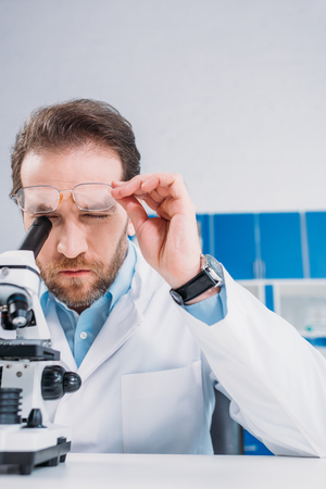 scientist in white coat and eyeglasses looking through microscope on reagent in laboratory