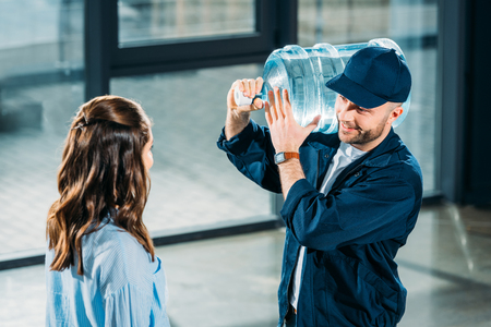 Woman looking at delivery man holding water bottle Reklamní fotografie