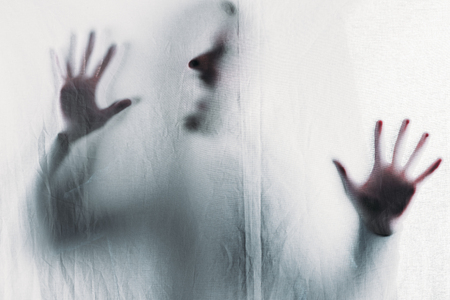 scary blurry silhouette of unrecognizable person screaming behind veil
