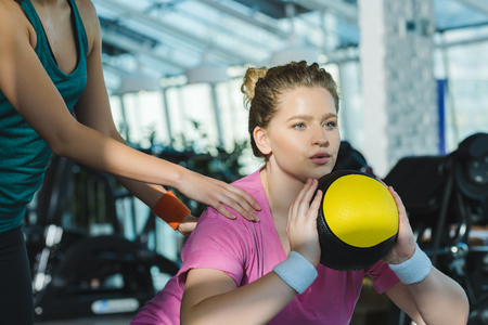 overweight woman training with medicine ball while trainer helping her