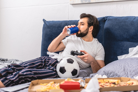 male loner playing video game and drinking beverage in bedroom Stock Photo