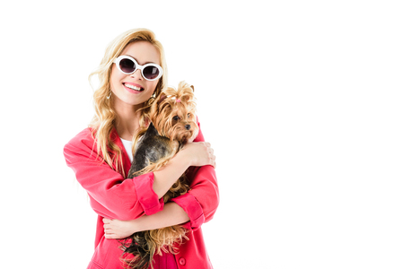 Young girl wearing pink jacket holding Yorkshire terrier isolated on white