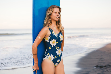 portrait of young sportswoman in swimming suit with blue surfing board behind on beach Stock Photo