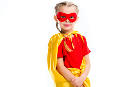 Portrait of little supergirl wearing yellow cape and red mask for eyes isolated on white