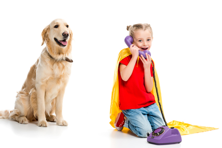 Beige dog with smiling little supergirl talking on phone and wearing yellow cape isolated on white