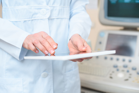 cropped shot of obstetrician gynecologist using tablet with ultrasonic scanner on background