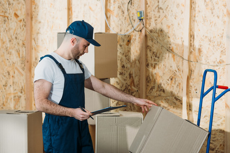 Delivery man comparing cardboard boxes and cargo declaration Stock Photo