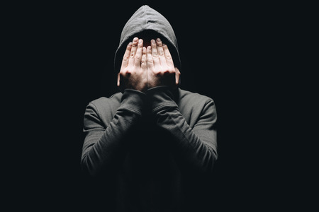 cropped shot of man in hoodie closing eyes with hands isolated on black