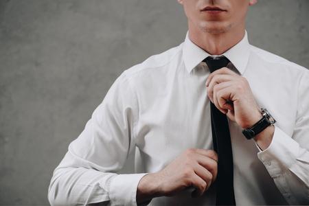 cropped shot of businessman adjusting necktie on grey