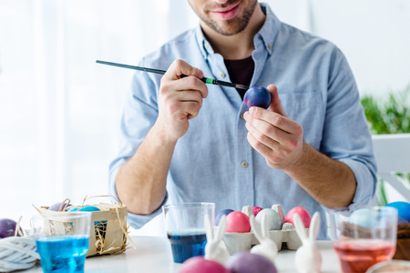 Close-up view of man painting Easter eggs Stock Photo