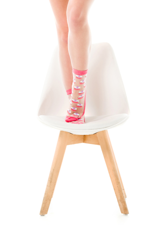 Woman in pink socks standing on chair isolated on white Stockfoto