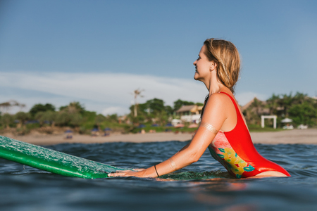 side view of young attractive woman in swimming suit resting on surfing board in ocean with coastline on background Stock Photo