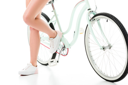 Close-up view of woman standing by bicycle isolated on white