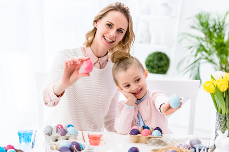 Mother and daughter showing colored Easter eggs Stock Photo