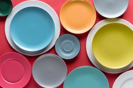 Pilas de platos de porcelana de colores sobre fondo rojo.