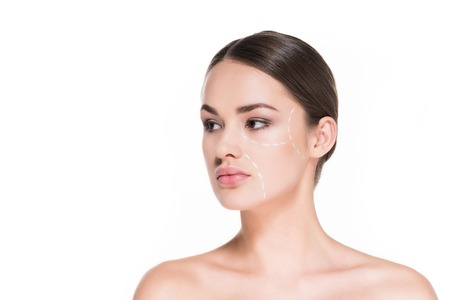 beautiful young woman with dotted line drawn on face for plastic surgery isolated on white Foto de archivo - 111577557