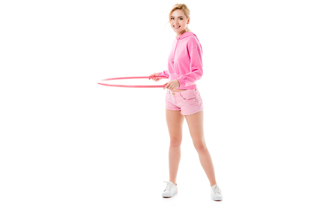 Young girl wearing pink exercising with hula hoop isolated on white Banque d'images