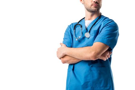Nahaufnahme eines Krankenpflegers in blauer Uniform mit Stethoskop, der mit verschränkten Armen isoliert auf weiß steht
