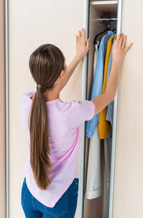 rear view of young woman opening cabinet with clothes at home
