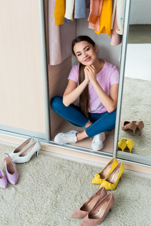 attractive young woman sitting inside of cabinet with various shoes on floor at home