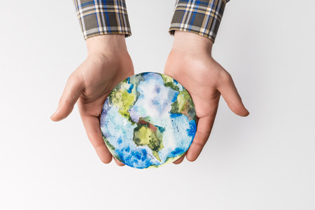 partial view of man holding handmade globe in hands isolated on grey, environment protection concept