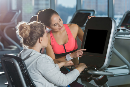 overweight woman starting to doing cardio while trainer helping her Stockfoto