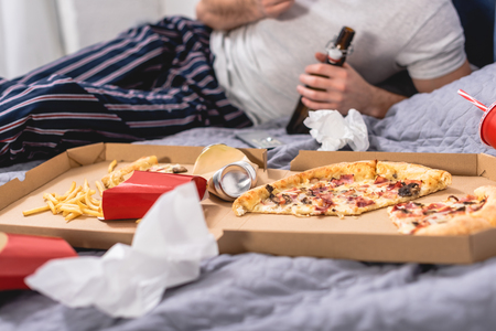 cropped image of loner eating pizza with beer on bed in bedroom