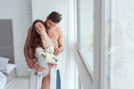 young man hugging girlfriend in white underwear with bouquet of roses at window 免版税图像