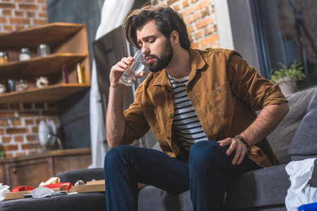 handsome loner drinking water while having hangover in morning at living room