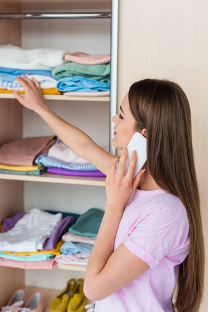 attractive young woman choosing clothes from cabinet and talking by phone Stock Photo
