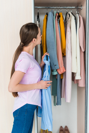 attractive young woman choosing clothes from cabinet at home Stock Photo - 111577600