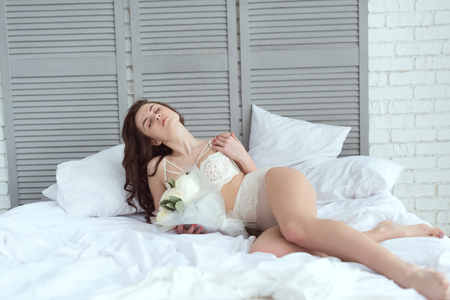 sexy woman in white underwear with bouquet of roses resting on bed 免版税图像