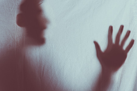 scary blurry silhouette of unrecognizable person screaming behind veil Reklamní fotografie - 111580433