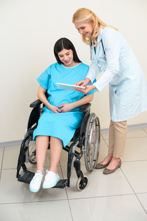 obstetrician gynecologist showing digital tablet to pregnant woman on wheelchair