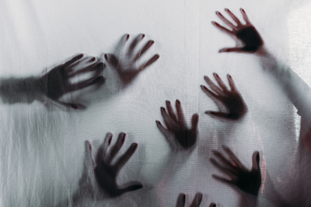 blurry scary silhouettes of human hands touching frosted glass Banque d'images - 111579539