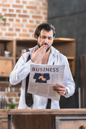 handsome loner businessman reading newspaper and yawning at kitchen