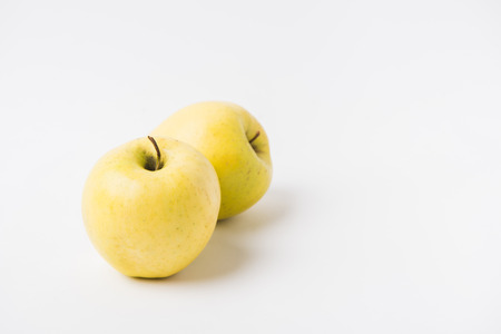 raw apples laying on white background
