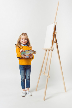 adorable little child with paint brush and palette standing near canvas on easel on white